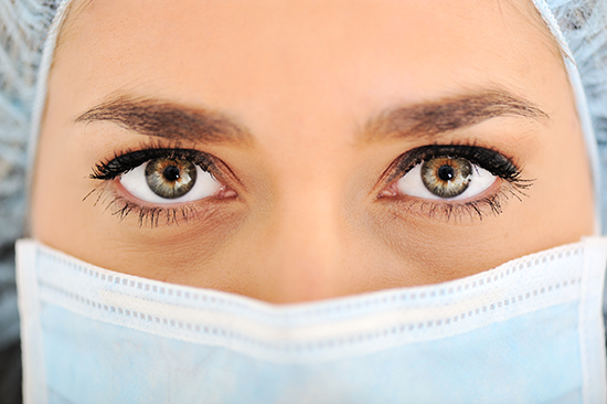 A photo closeup of the face of a women wearing a surgical mask.